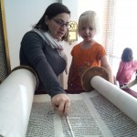 A Shorashim learner follow along as Morah Shif reads the Shema from the Torah.