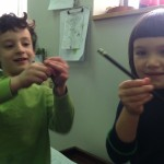 A pair of Nitzanimers using pencils to show the angle of their mezuzah on the door.