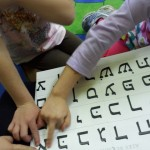 Shorashim learners point at the letters of the Hebrew alphabet as we sing the Aleph Bet song during Zman P&#039;Geesha (meeting time).