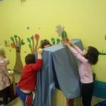 The children set the stage for their puppet drama