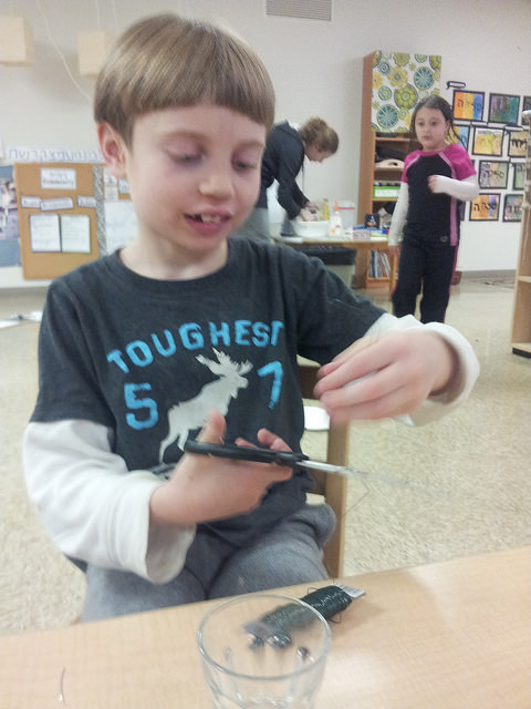 A second grader creates using wire.