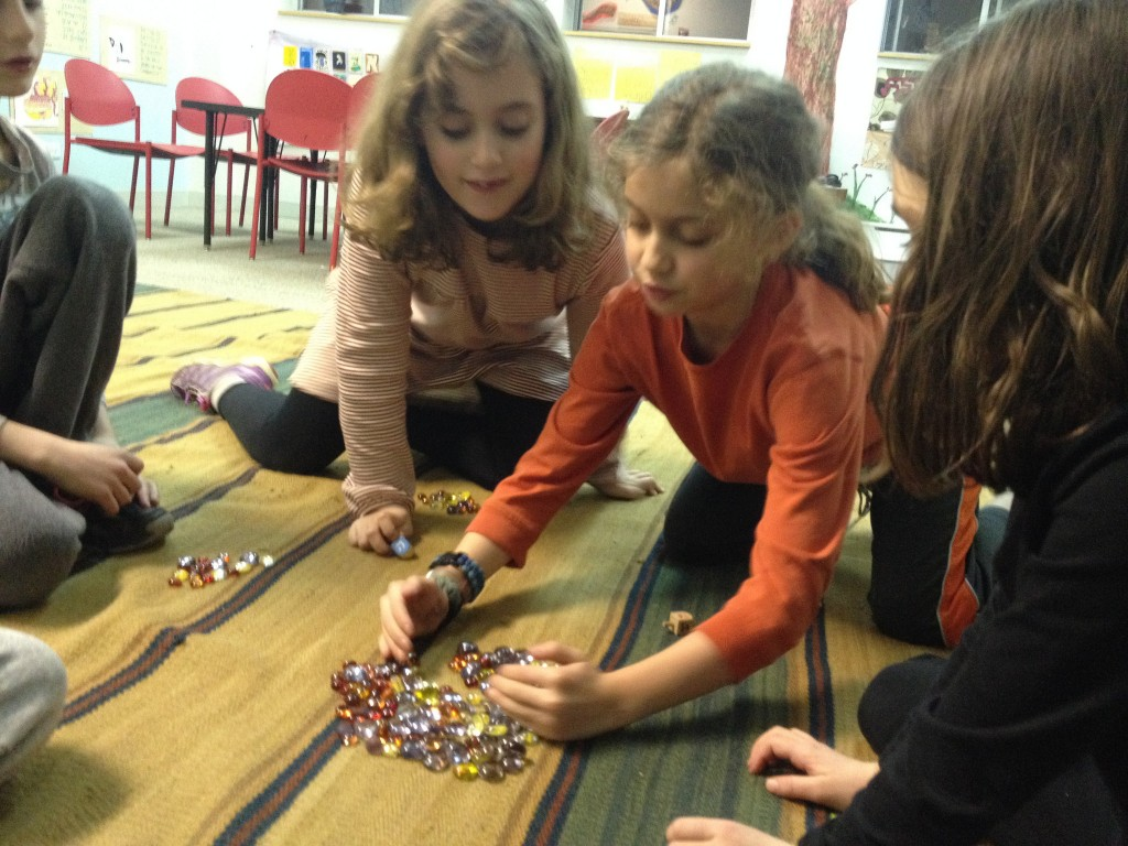 Girl 3, 1 and 2 (left to right) playing dreidel.