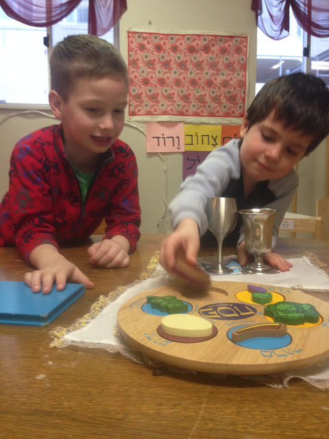 A four year old and a five year old set the table for a Passover Seder.