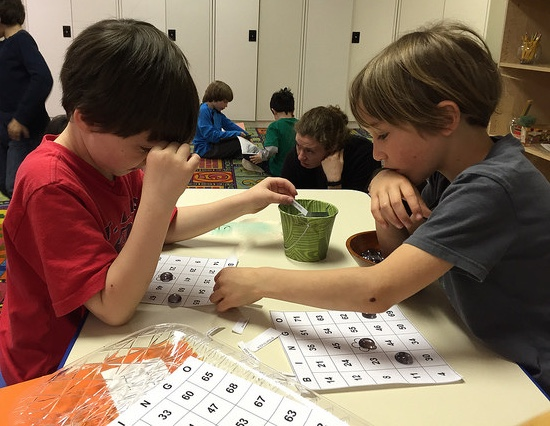 A first grader and a second grader play bingo together.
