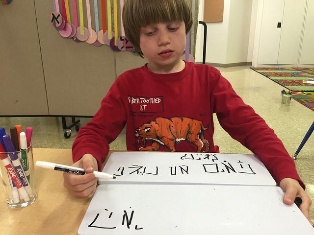 A second grader writes sentences in Hebrew.
