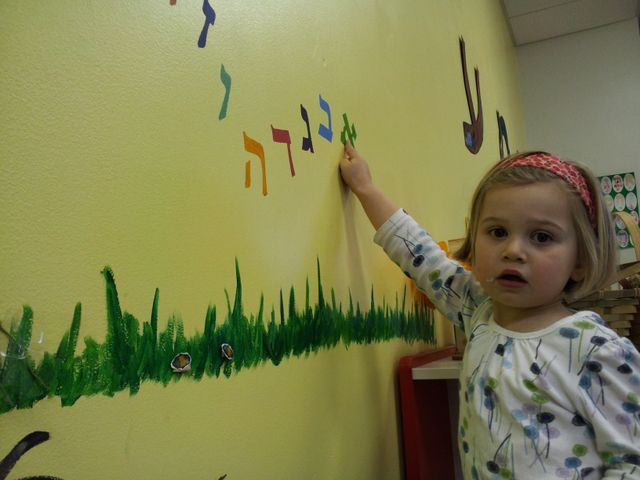 "A Shorashim learner points to ""Aleph"" on our classroom wall mural"