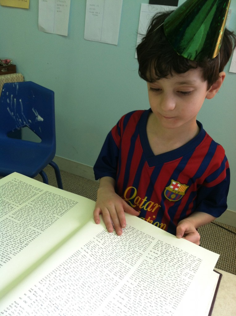 Personal project: to look through all 10 volumes of the Shulchan Aruch in our room. Not even a party hat will distract him.