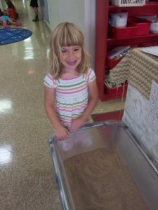 A child practices her otiot on the sensory table
