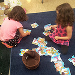 Two kindergarteners working together on a puzzle.