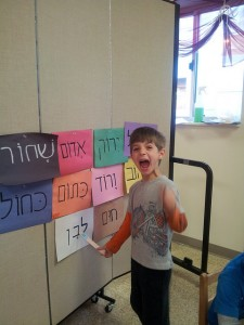 A first grader matches צבעים (tzevaim—colors) with their labels.