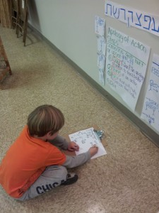A second grader copies the steps of apology of action into the book he's making.