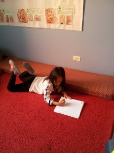 A first grader concentrates on capturing her feelings after our guided mediation.
