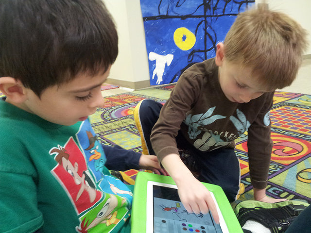 A first and second grader work on using the Book Creator app to make their hallel book.