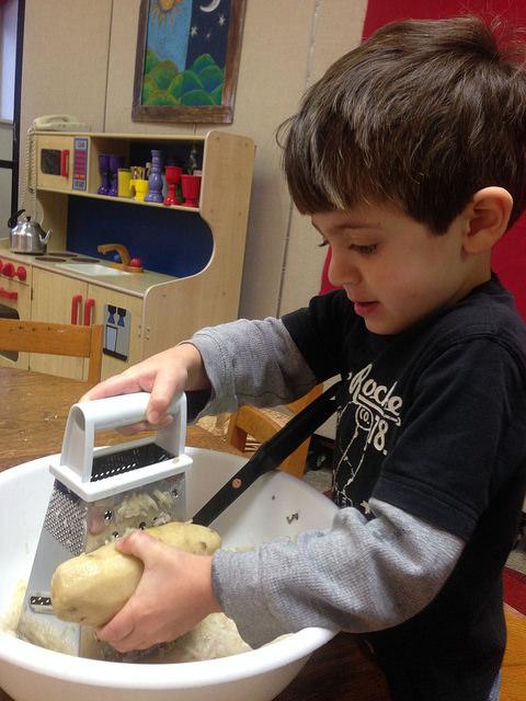 Grating the potatoes.