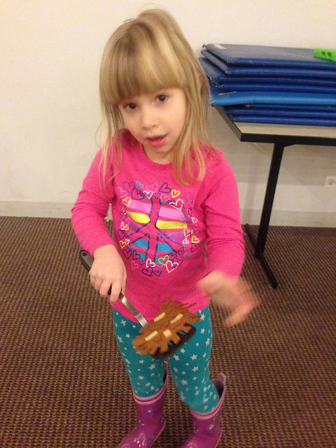 A four year old carries her Latke across the room on a spatula during our relay.