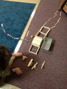 "A team of two built this structure based on Maccabees II. The popsicle stick roof is like a sukkah, and the line of stones is ""Jewish people waiting to get into the temple."" The kindergartener whose hands you see is touching ""a rabbi lighting the lamp."" She was acting out the lighting."