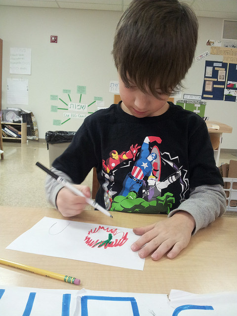 A first grader working on a drawing of the burning bush scene.
