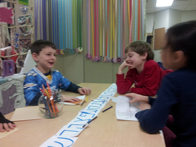 Three second graders laugh together as they talk about the mountain of God.