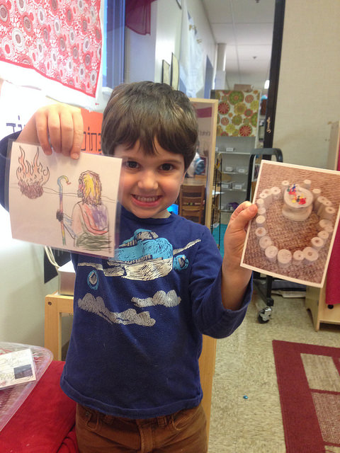 A three year old matches an illustration of the Burning Bush to the building he created of it.