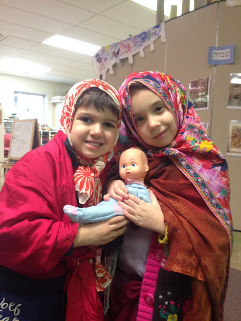 A three year old and a kindergarten act out one of the scenes from the story we have been hearing. One of them plays Moshe, one is Tzipporah and they are holding their new son Gershom.
