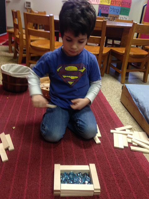 A four year old builds a basket for baby Moshe.