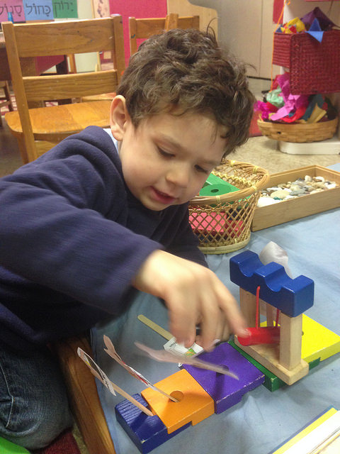 A three year old builds the scene from our story of the Israelites and Egyptians fighting.