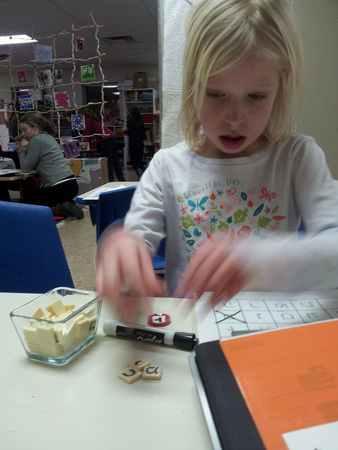 A first grader completes the bananagram and vowels activity.