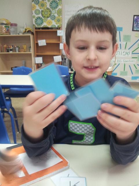 A second grader plays Go דג (dag—fish).