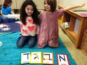 Two Shteelimers sharing materials to create the aleph bet together