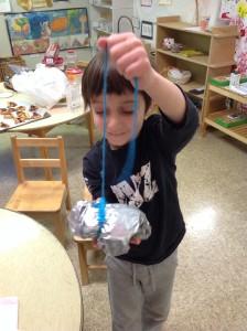 A Shteelimer wraps hamantaschen he made for his grandma.