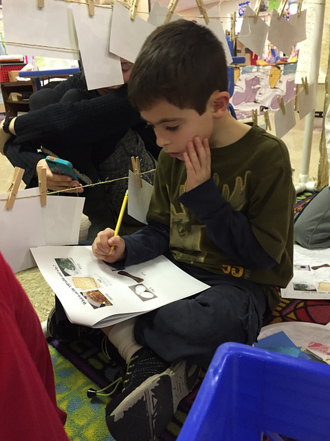 A second grader writes his interpretation for the items on the seder plate.