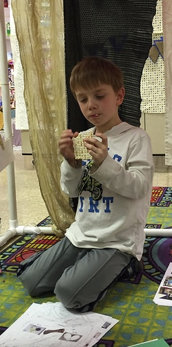 A first grader enjoys his מצה (matzah).