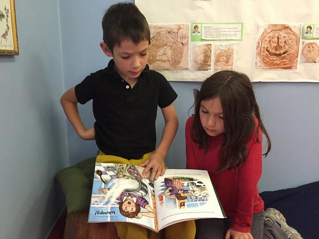 A kindergartener reads to a third grader.