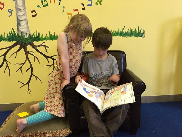 A first-grader and kindergartener read together.