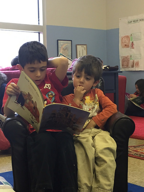 A second grader reads to a three-year-old.