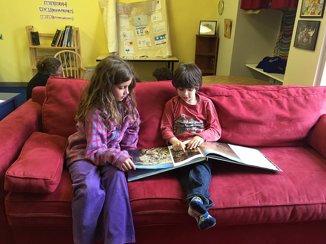 A first grader and third grader read together.