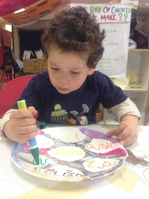 A four year olds writes the name of the Seder plate items on his plate.