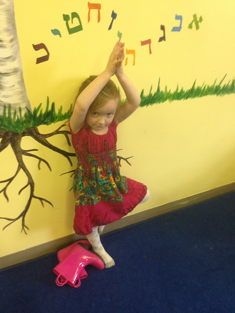 A four year old practices tree pose during yoga.