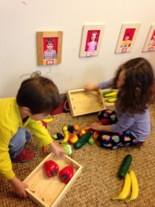 A kindergartener and 4-year-old work together to harvest and sort crops.