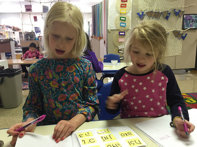 Two first graders working on inventive spelling in script.