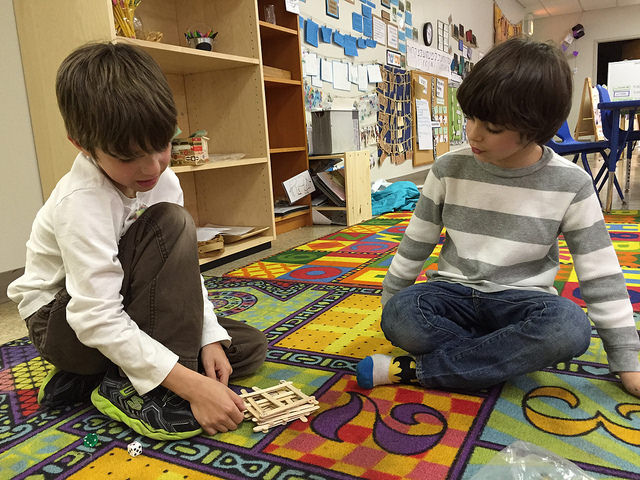 Two first graders play a pick-up-sticks game they invented.