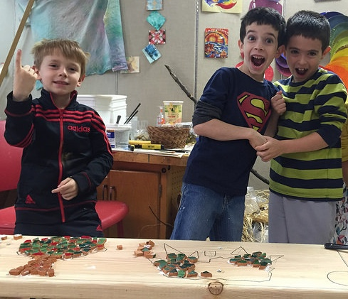 Two first graders and a second grader show off the mosaic work they've done.